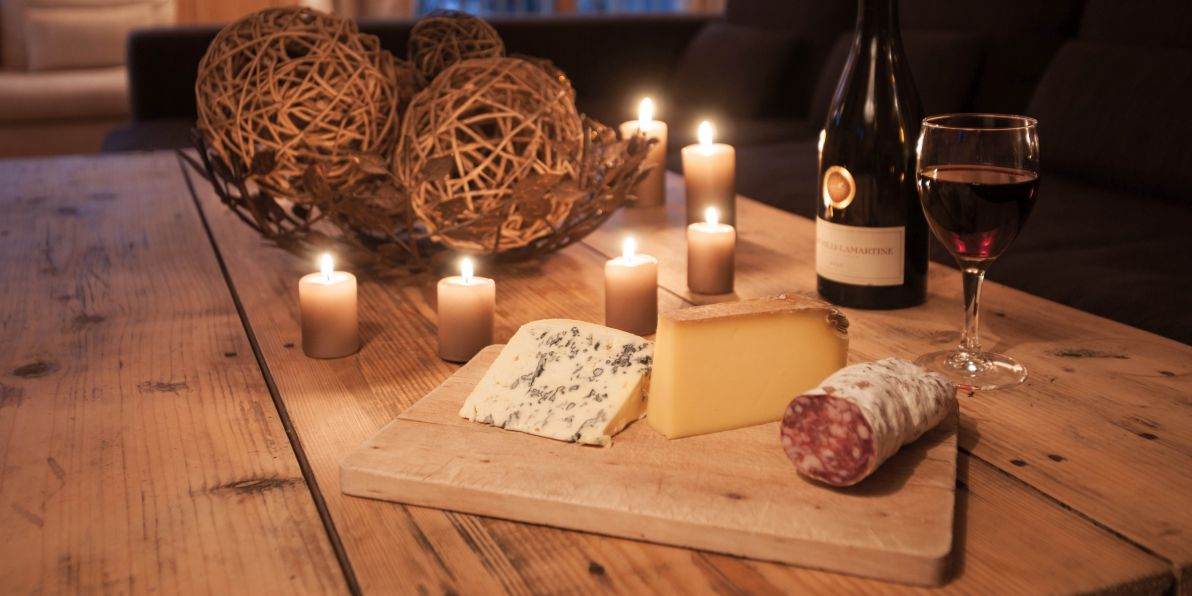 Cheese board, wine and candles in Chalet La Chouette